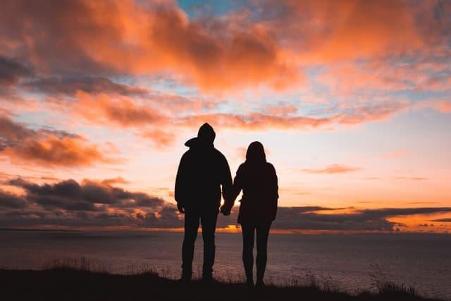 Amoureux se tenant la main, regardant le coucher de soleil.